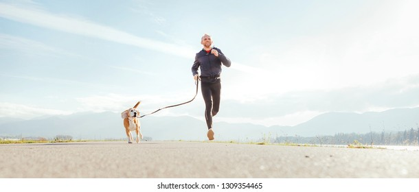Running man with his dog . Active healthy lifestyle concept image.