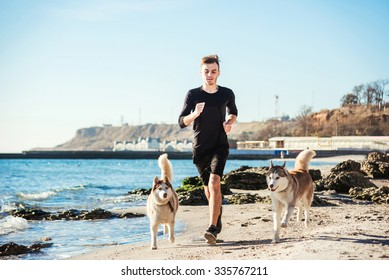 Running man. Male runner jogging with siberian husky dogs during the sunrise on beach
