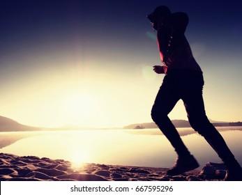 Running man on beach. Sportsman run in baseball cap, jogging guy during the sunrise above sandy beach. Man jumping on the beach at sunset