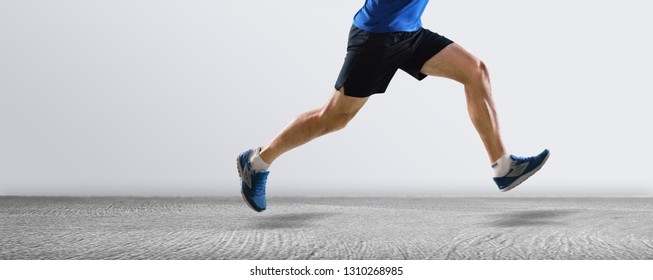 Running man runner training doing outdoor city run sprinting along wall background. Urban healthy active lifestyle. Male athlete doing sprint hiit high intensity interval training. Banner panorama