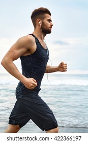 Running Man. Sporty Runner Enjoying Run By Sea During Outdoor Workout. Handsome Fit Athletic Male Jogging On Beach. Healthy Active Jogger Exercising And Training For Marathon. Fitness, Sports Concept