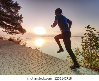 Running man wear dark running shoes and trendy  sports clothes. Sportsman exercising at lake shore or river bank.