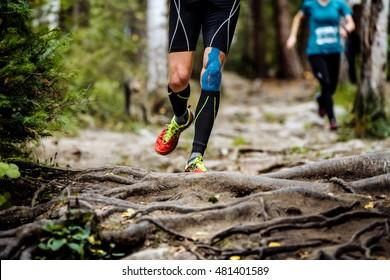 running marathon runner in forest. legs in compression socks, knee taping