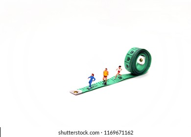 Running Mini Figure man and woman at green tailor meter, white background
