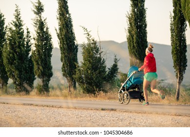 Running mother with child in baby stroller enjoying sunset and mountains landscape. Jogging or power walking supermom, active family at sunset. Beautiful inspirational mountains landscape.
