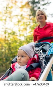 Running mother with contemplative child in stroller enjoying motherhood at autumn sunset and forest landscape. Jogging or power walking woman with pram in woods.