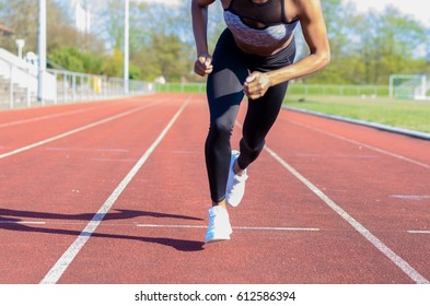 Running muscular legs of a young athlete training or working out on a sports track in a low angle view along the lane