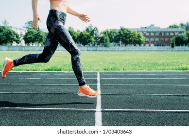 running outdoors in the stadium. legs in sportswear and fashionable sneakers. cross stodion