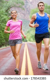 Running people - two runners jogging on road in beautiful nature training for marathon run. Multiracial sports couple, Asian woman sport model and man fitness model exercising together smiling happy.