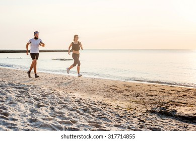 Running people - woman and man athlete runners jogging on beach. Fit young fitness couple exercising healthy lifestyle outdoors during sunrise or sunset