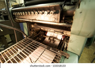 Running printing press with printed pages coming down the line.