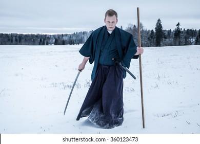 running Samurai with japanese sword in snowy field