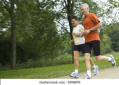 Running senior couple with motion in the picture. Focus is on the woman.