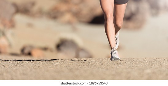 Running shoe closeup of woman running on gravel path with sports shoes