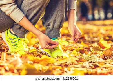 Running shoes. Barefoot running shoes closeup. Female athlete tying laces for jogging on autumn road in minimalistic barefoot running shoes. Runner getting ready for training in fall. Sport lifestyle.