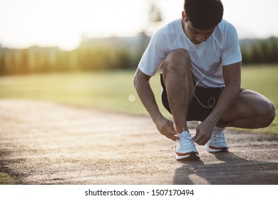 Running shoes. Barefoot running shoes closeup. male athlete tying laces for jogging on road in the park running shoes.