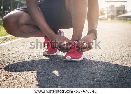 Running shoes. Barefoot running shoes closeup. Male athlete tying laces for jogging on road in minimalistic barefoot running shoes. Runner getting ready for training. Sport lifestyle.
