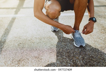 Running shoes, Close up of runner man trying shoelaces getting ready for run on the outdoor street. Sport and exercise concept