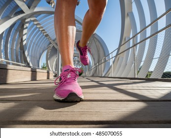 Running shoes closeup of a female runner on a modern bridge. Running and sport lifestyle at the city concept.