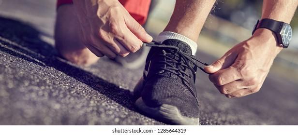 Running shoes - closeup of man tying shoe laces.