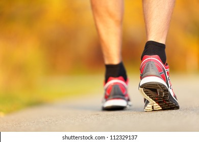 Running shoes closeup. Runner on road in fall autumn colors - closeup of male running walking shoes of jogger outdoors.
