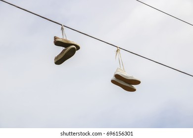 Running shoes hanging from an electric wire.