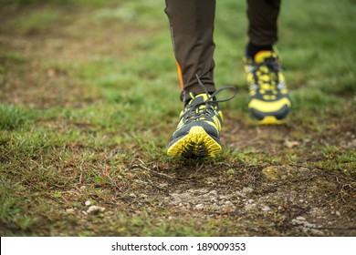 Running shoes of a man jogging cross country outdoor in spring