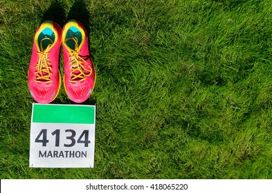 Running shoes and marathon race bib (number) on grass background, sport, fitness and healthy lifestyle concept