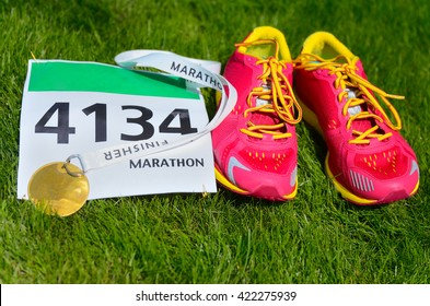 Running shoes,  marathon race bib (number) and finisher medal on grass background, sport, fitness and healthy lifestyle concept