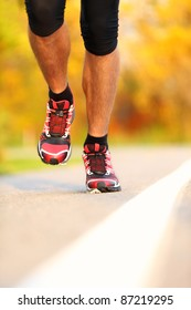 Running shoes on runner outdoors. Closeup of man jogging and training for marathon.