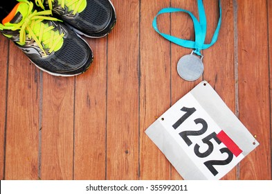 Running shoes, race bib and a medal after an excellent athletic competition