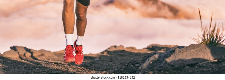 Running shoes of runner training endurance on trail run outdoors in mountains background. Panoramic banner.