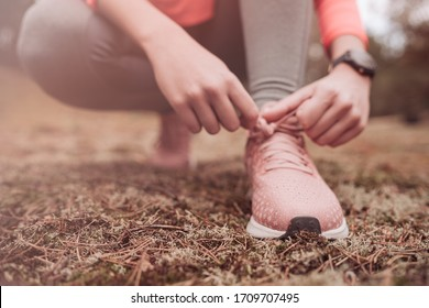 Running shoes - woman tying shoe laces. Closeup of female sport fitness runner getting ready for jogging outdoors on forest path in spring. Runner tying her shoes preparing for a run a jog outside.