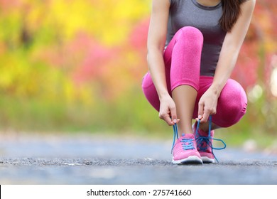Running shoes - woman tying shoe laces. Closeup of female sport fitness runner getting ready for jogging outdoors on forest path in late summer or fall.