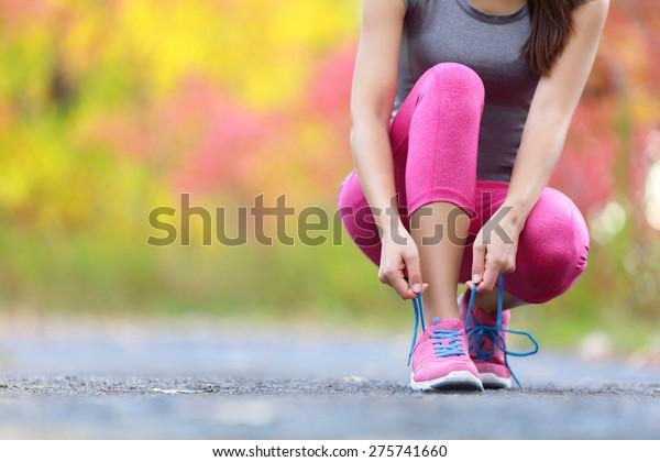 Running Schuhe - Frauen binden Schuhlaken. Nahaufnahme der sportlichen Fitness-Läufer, die sich im Spätsommer oder Herbst für Joggen im Freien auf dem Waldweg vorbereiten.
