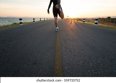Running shoes - young fitness  runner stretching legs before run. male sport fitness runner getting ready for jogging outdoors the time during sunrise on dam road exercise