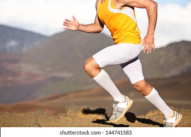 Running sport fitness man. Closeup of strong legs and shoes in action. Male athlete fitness runner sprinting fast outside in compression sports clothing, socks and tights shorts. Trail running concept