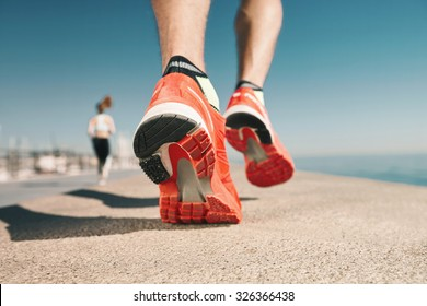 Running sport. Man runner legs and shoes in action on road outdoors at sunset. Male athlete model.