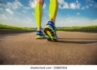 Running sport. Man runner legs and shoes in action on road outdoors at sunset.