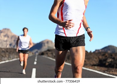 Running Sport. Runners on road in endurance run outdoors in beautiful landscape. closeup of man legs and torso with male runner in the background. Shallow DOF, focus on hips and arm.
