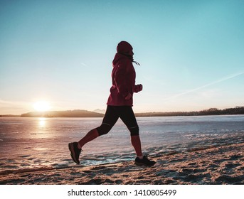 Running sport woman. Female runner jogging at cold winter bay  wearing warm sporty running clothing. Fitness happy girl