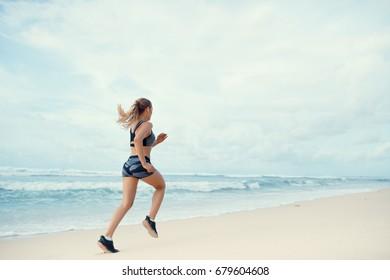 Running sports girl on the beach