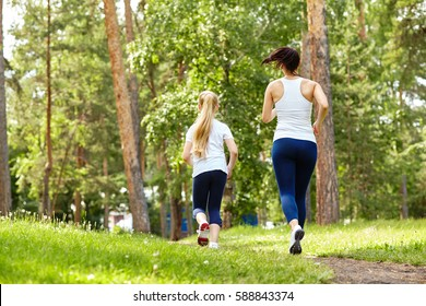 running sporty mother and daughter. woman and child jogging in a park. outdoor sports and fitness family
