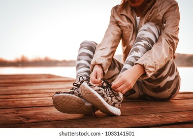 Running sporty woman tying running shoes