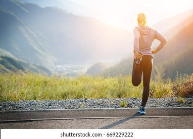 Running stretching. Athlete at the top of the mountain