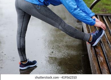 Running stretching. Closeup of running shoes, woman stretching leg as warm-up before run