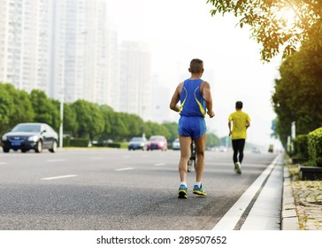 Running at sunrise exercising for marathon and workout fitness
