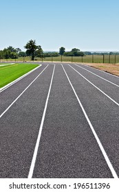A running track beside a field with some dirt.