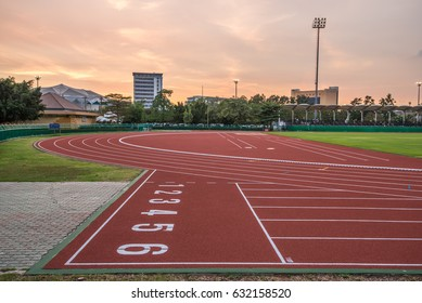 running track and field stadium on sunset