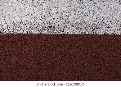 Running track and field texture background. Background of running track field surface closeup macro photo with white line.